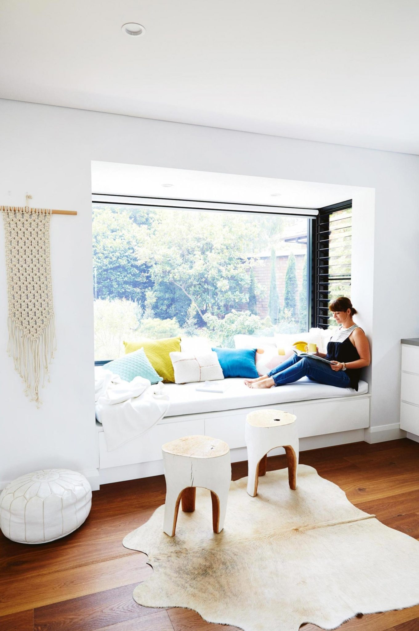 White sunlit window seat reading nook