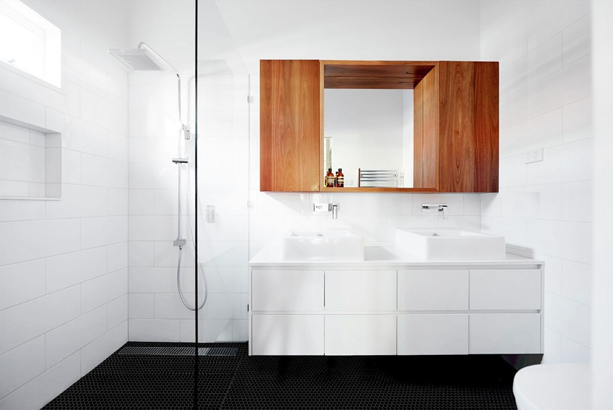 Wooden cabinet and dark floor bring contrast to the bathroom