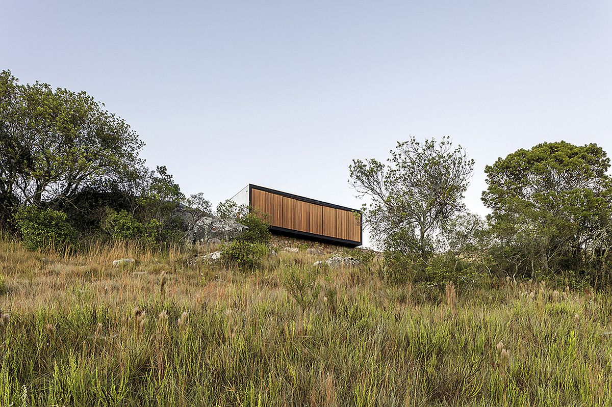 Wooden facade of the prefab can switch between unabated views and complete privacy