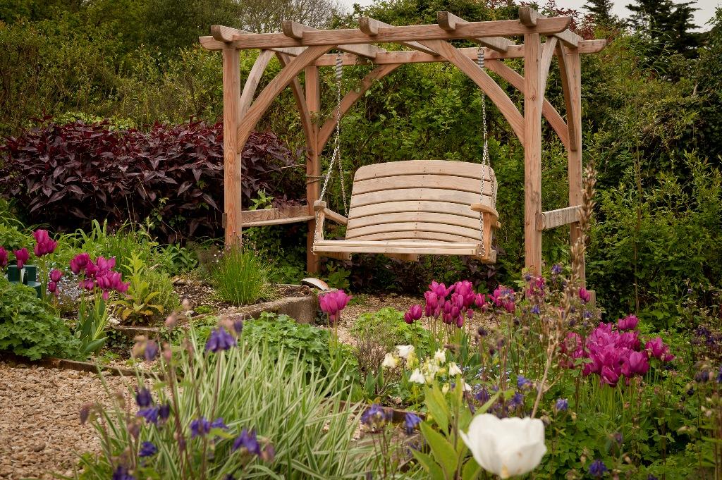 Wooden garden swing among flowers