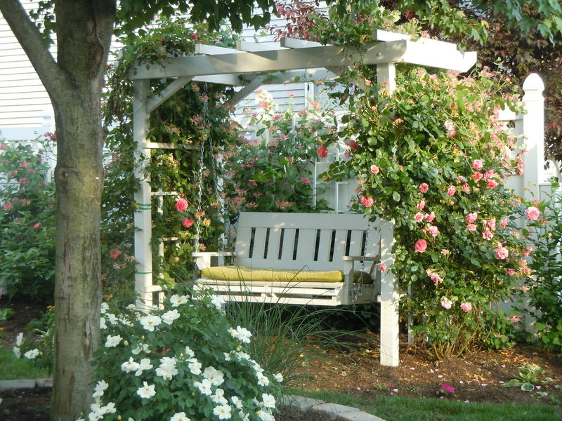 Wooden garden swing in a blooming floral atmosphere