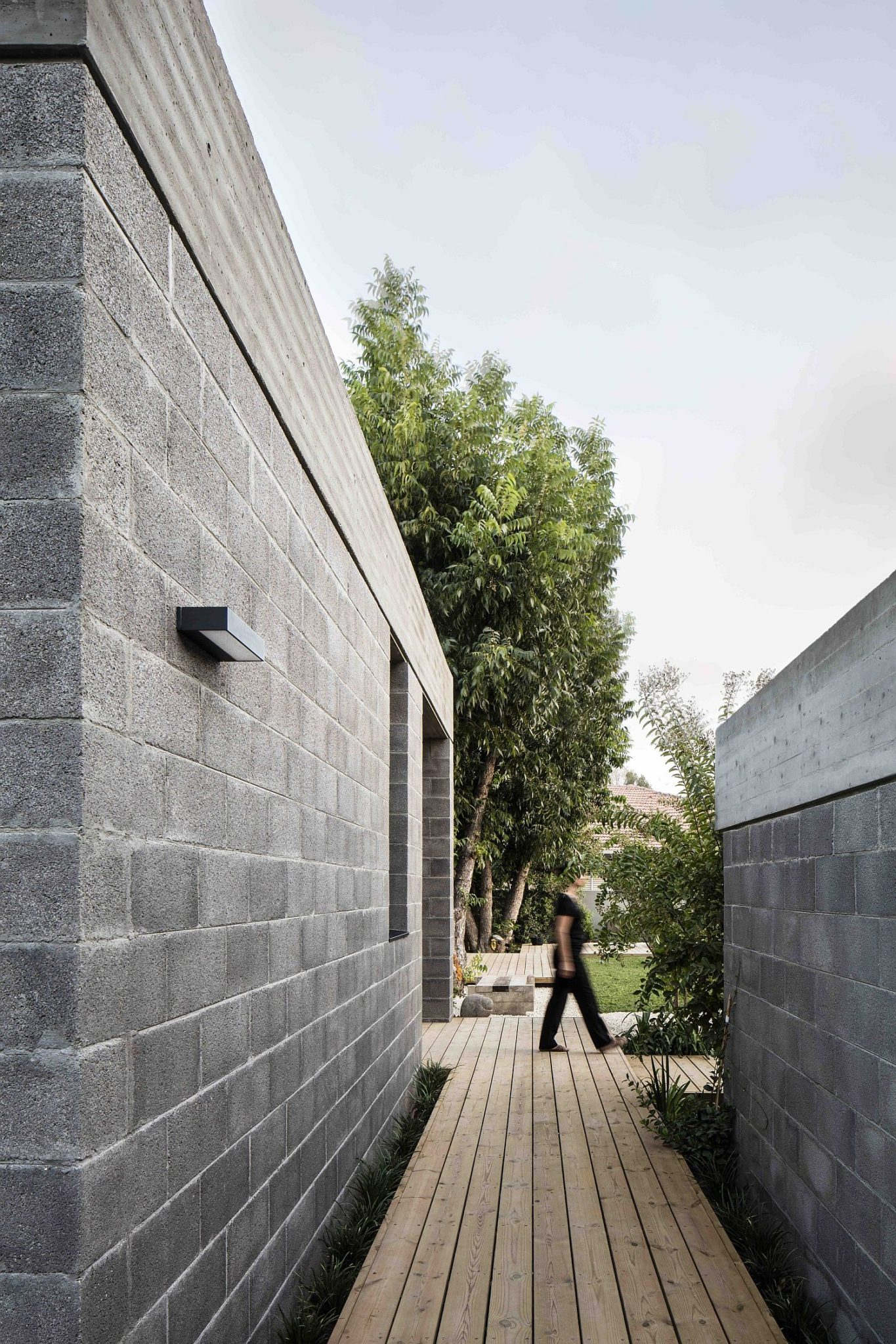Wooden walkways and garden spaces surround the family house