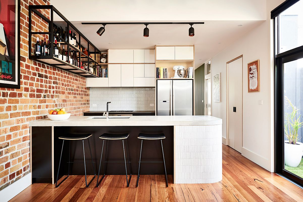 A curvy kitchen island adds contemporary flair to the industrial setting