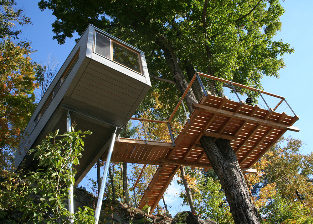 A modern treehouse with a deck in a shade of a tree