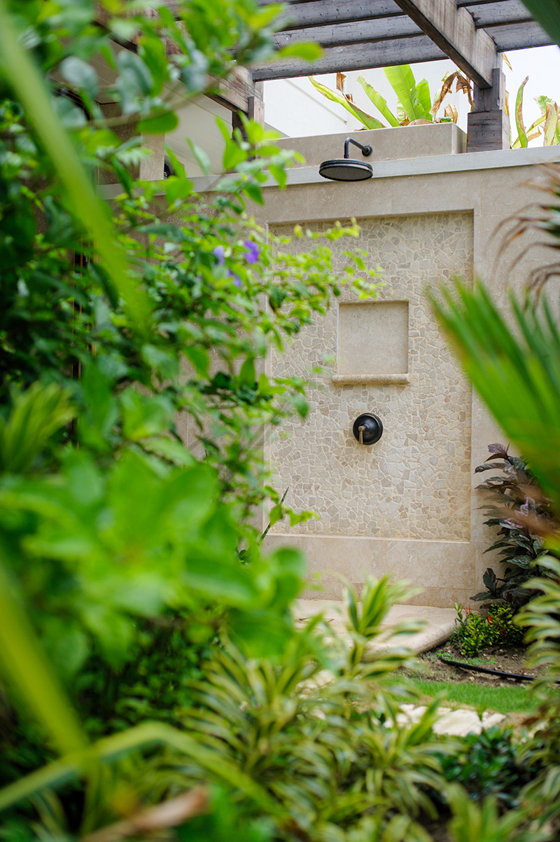 An almost hidden outdoor shower that grants privacy and comfort