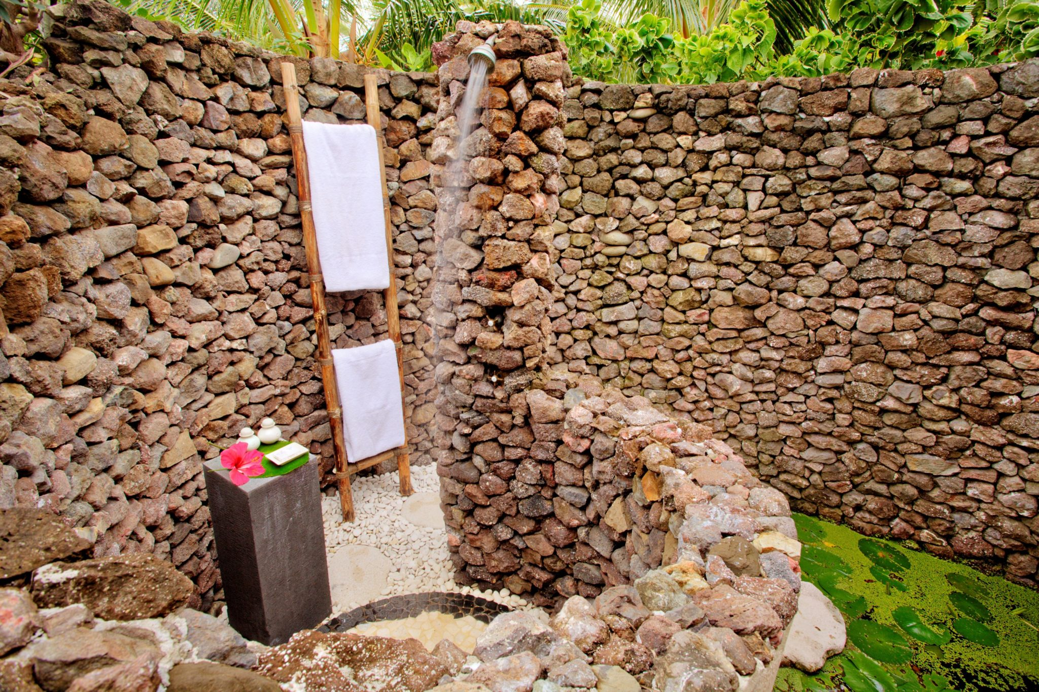 An outdoor shower made of countless little stones