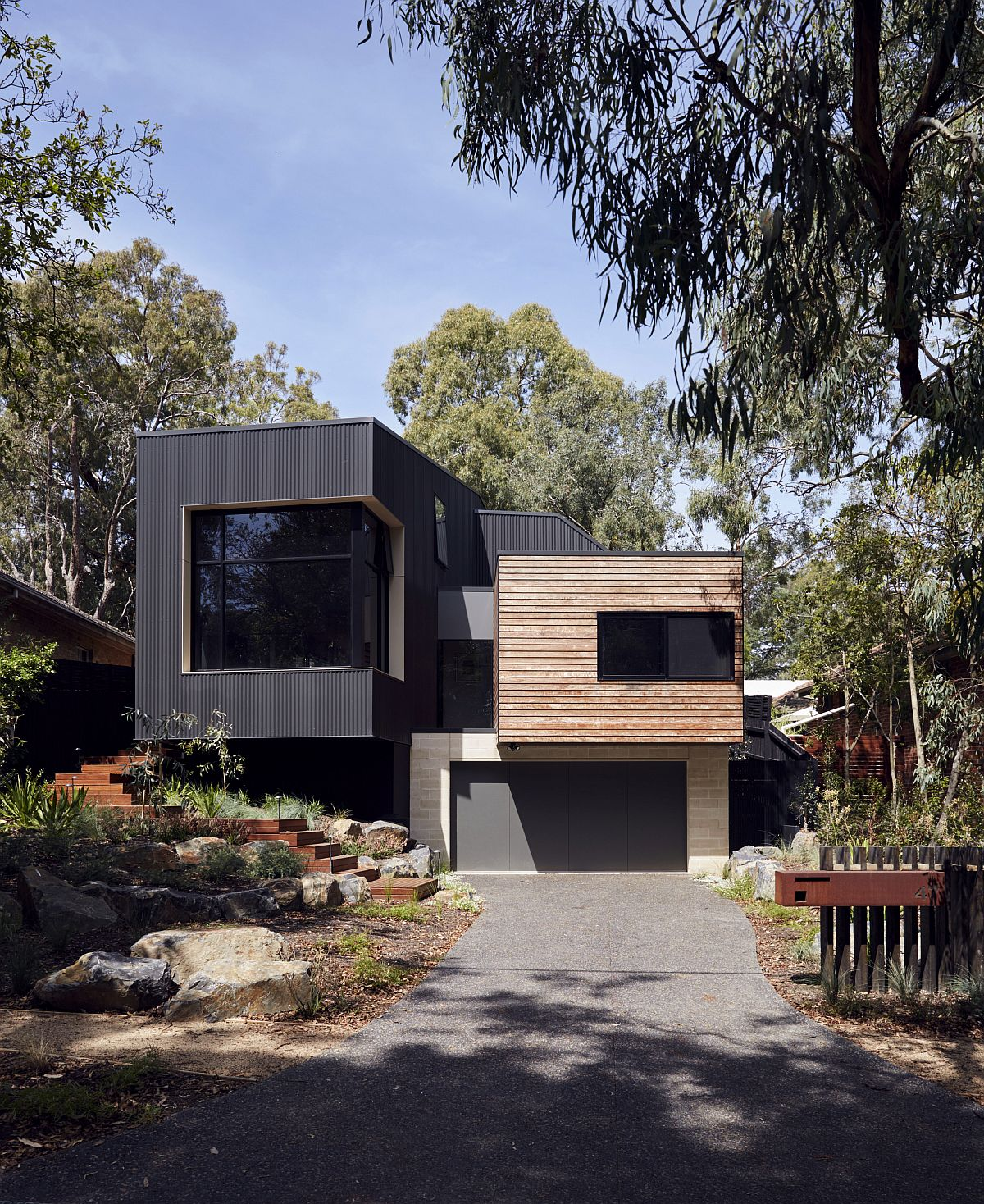 Cantilevered top level of the home with dark exterior stands out visually