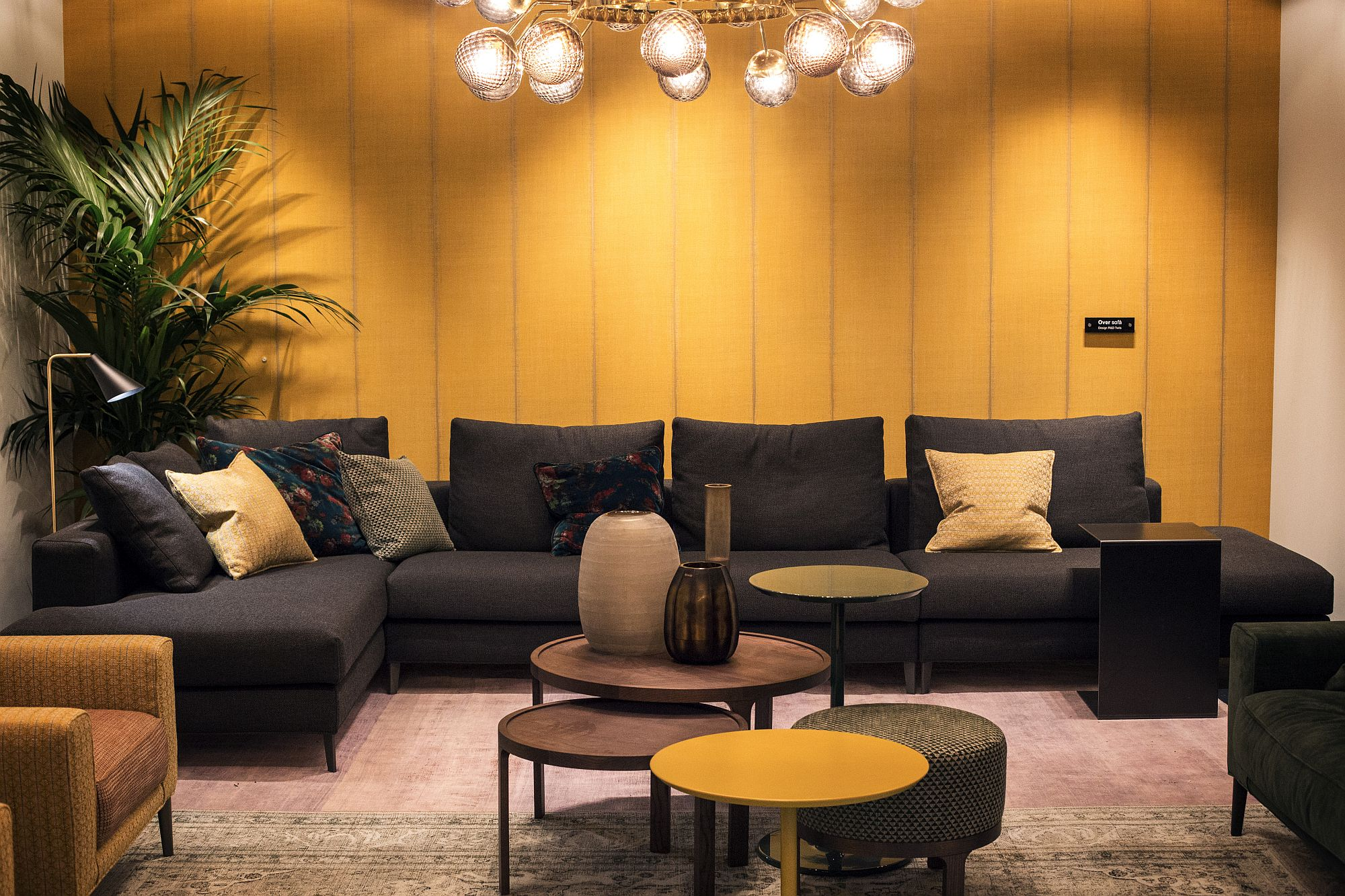 Cool orange coffee table complements the backdrop even as black couch brings style and elegance