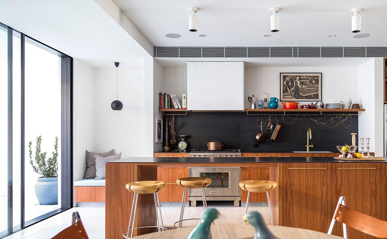 Kitchen with black backsplash, comfy seating and breakfast bar