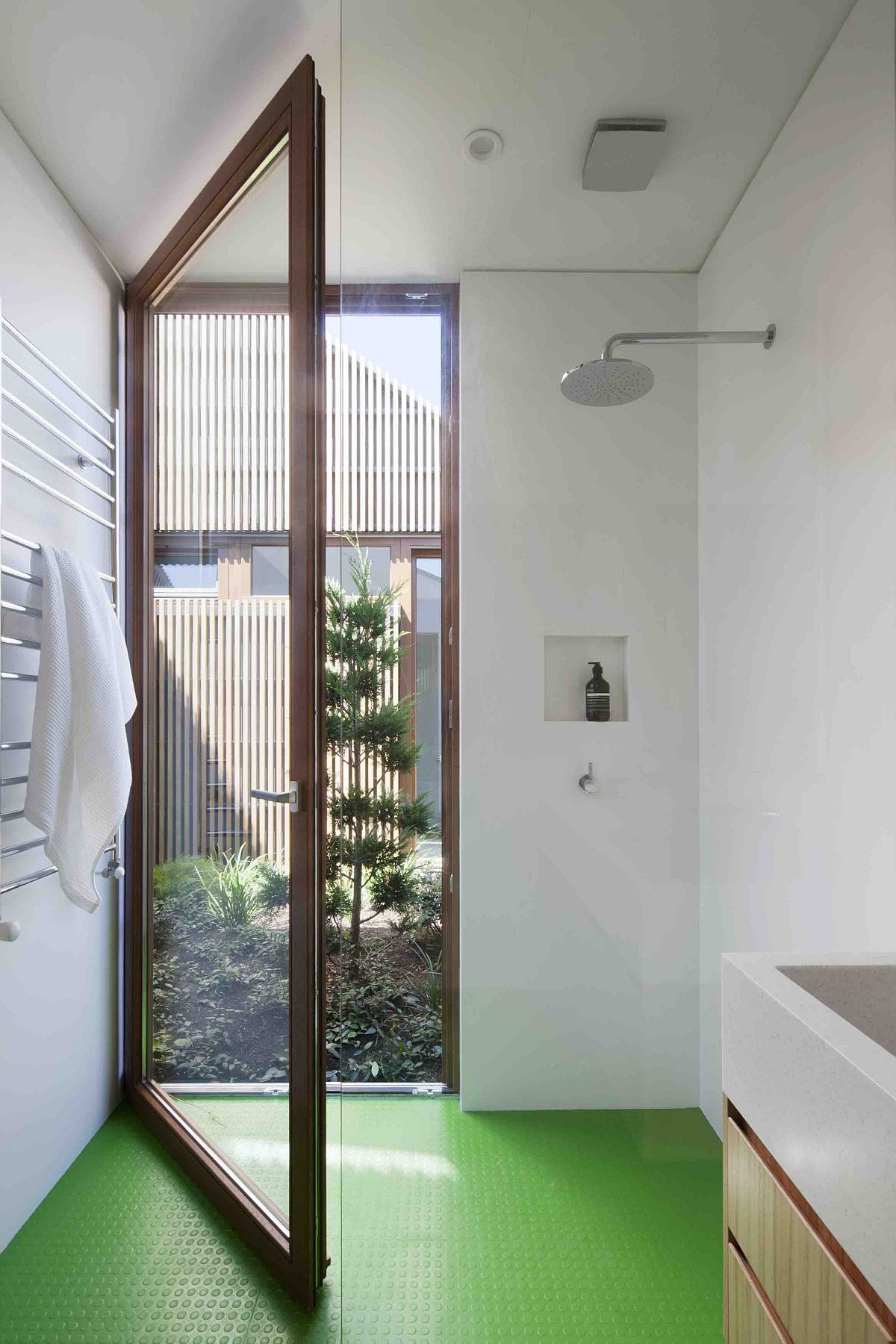 Large glass door connects the bathroom with the exterior