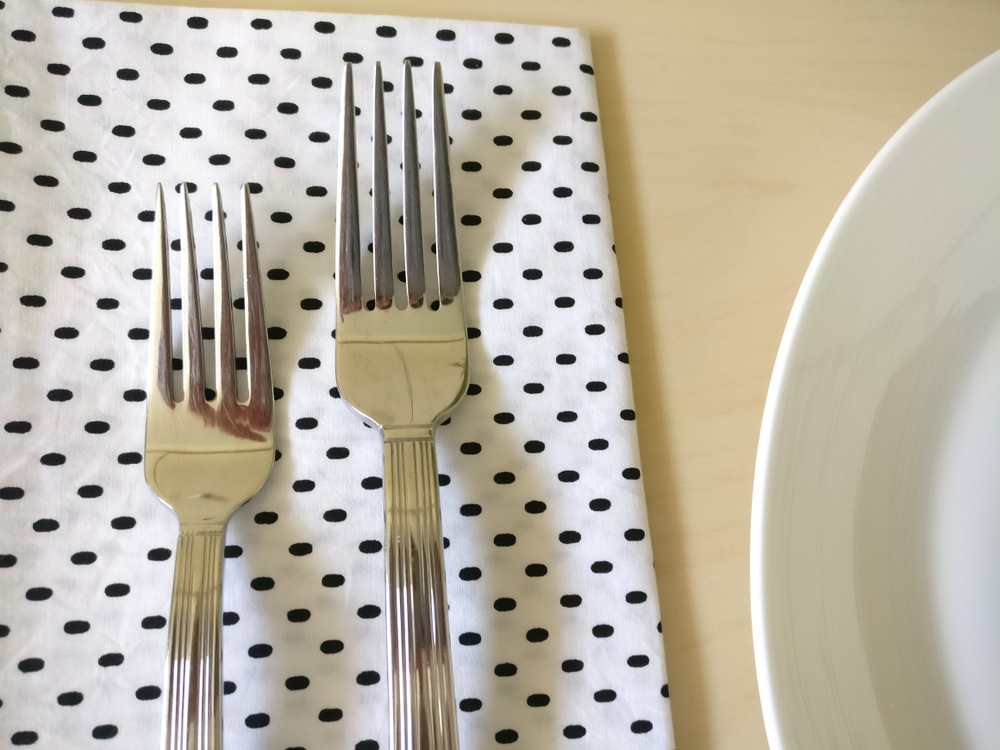 Silver flatware on a speckled napkin