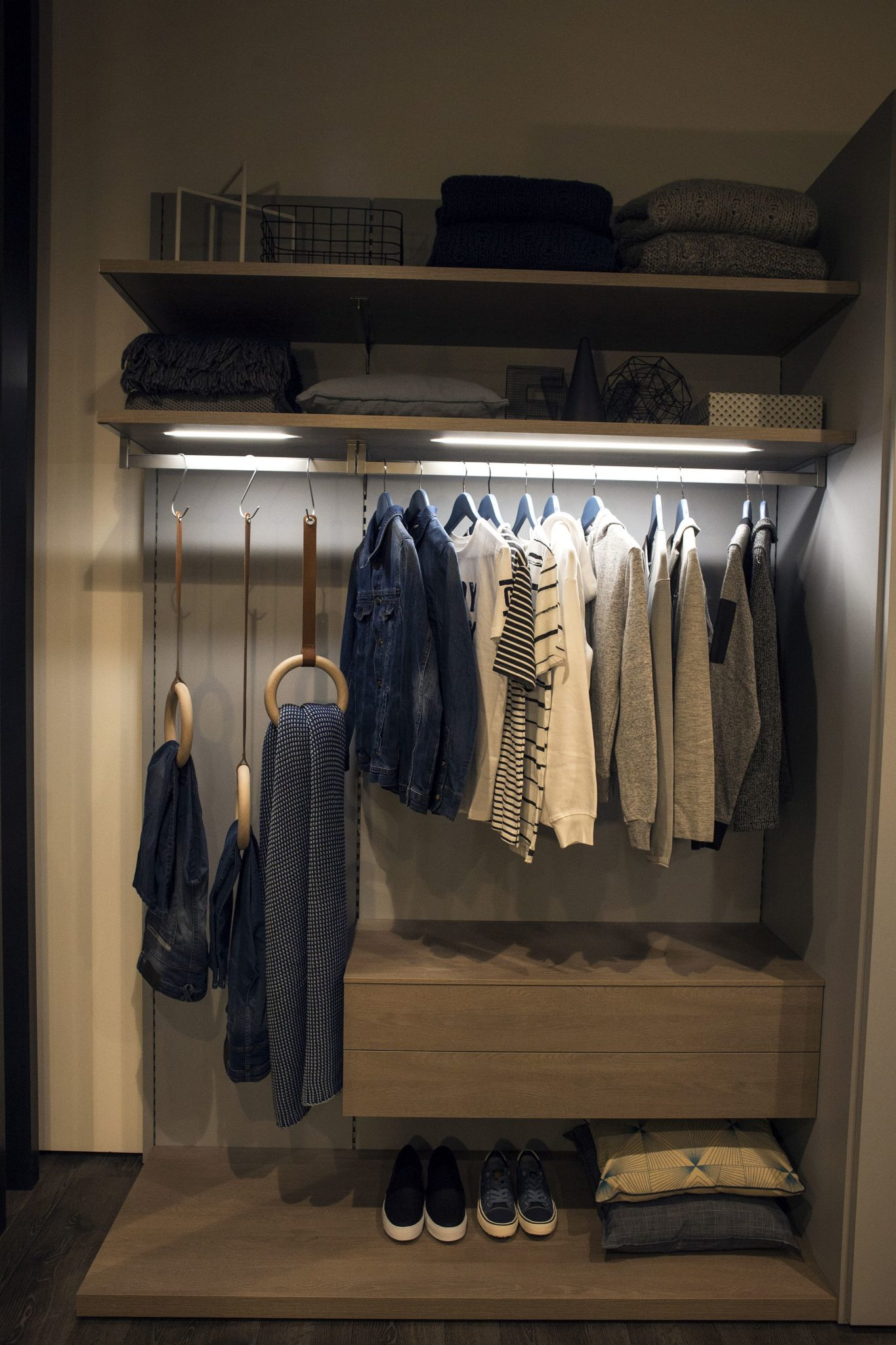 Sleek shelves and lighting combine to create a cool corner wardrobe