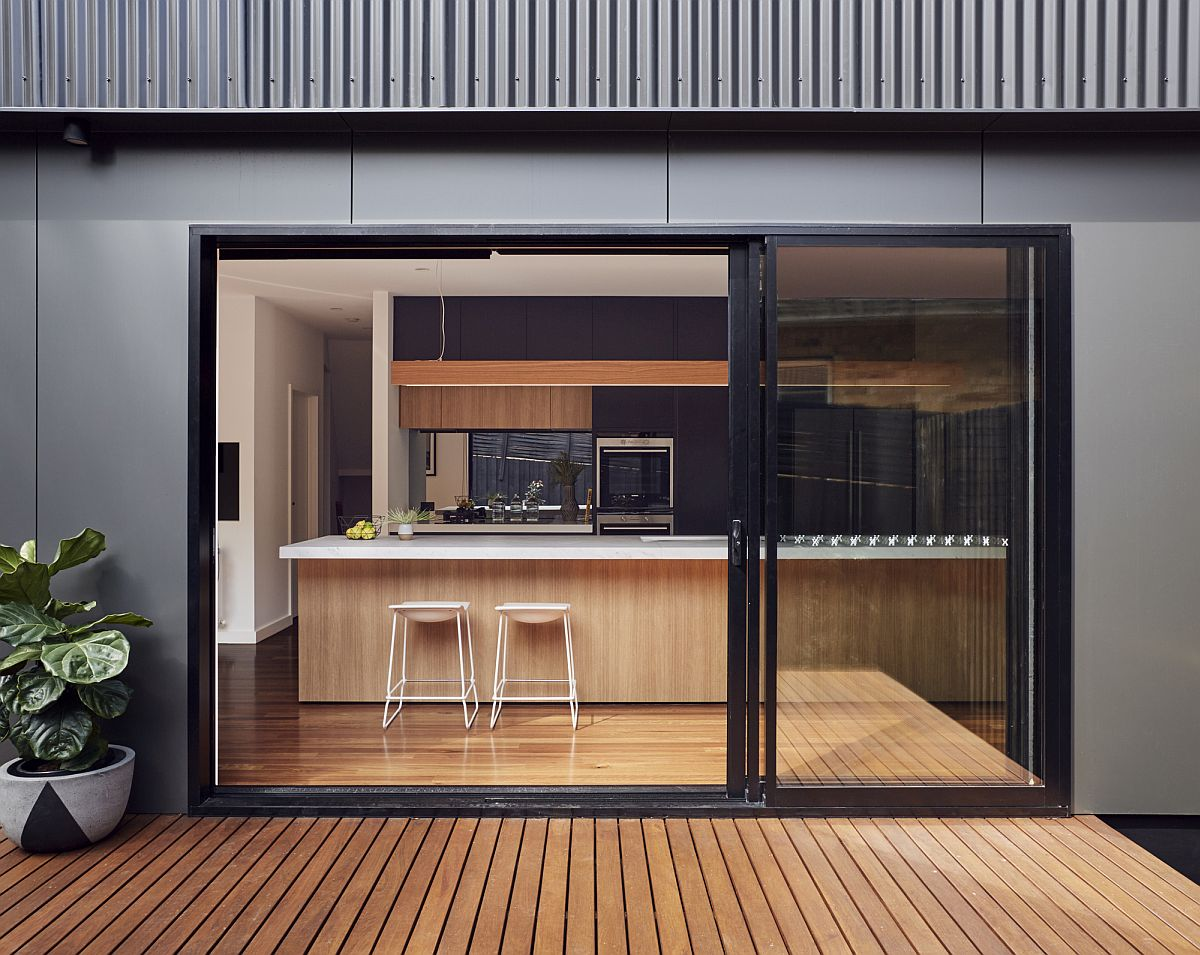 Sliding glass doors with drak frame connect the interior with the wooden deck