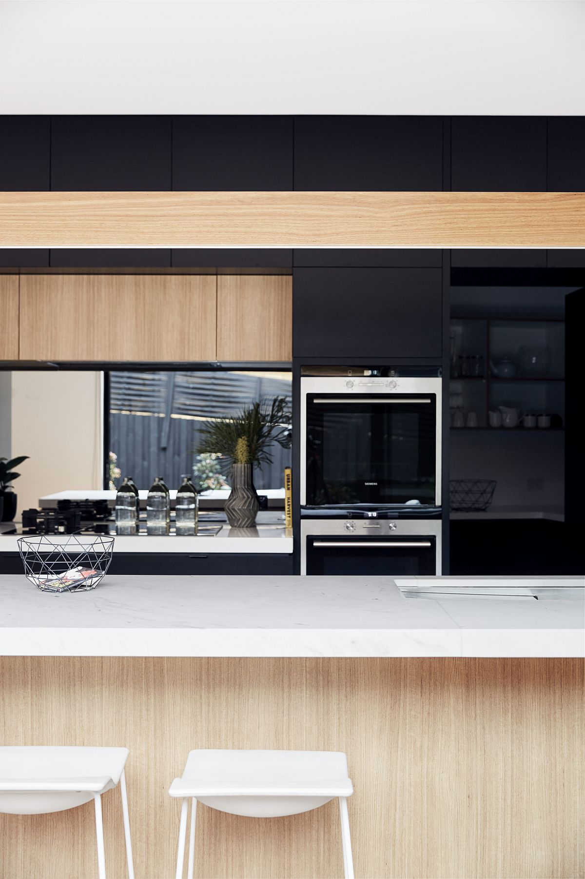 Smart modern kitchen combines black shelves with light wooden finishes