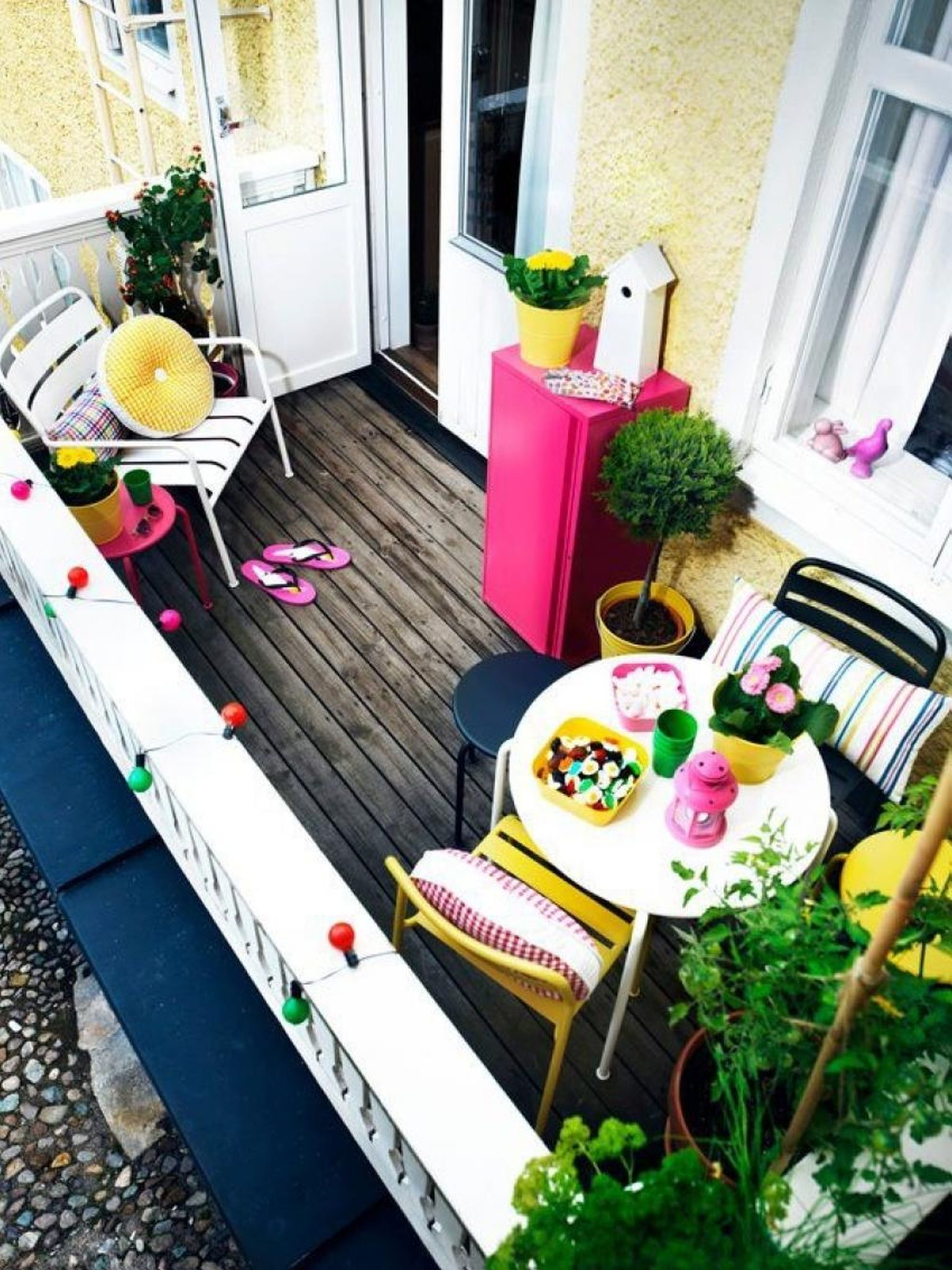 Tiny yellow balcony with a vibrant pink cupboard