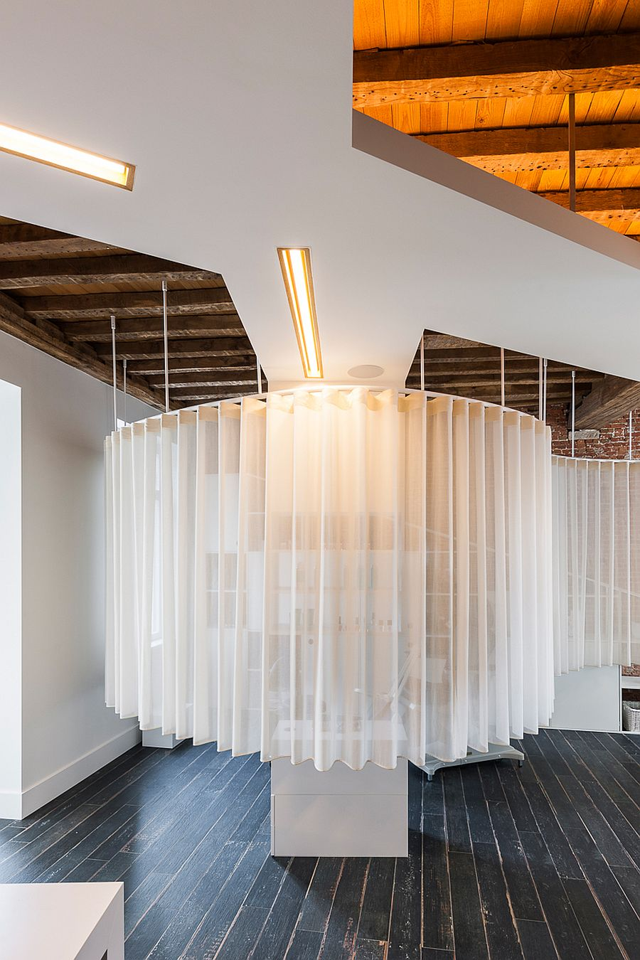 White ceiling, lighting with golden glint and smart design transform the industrial space