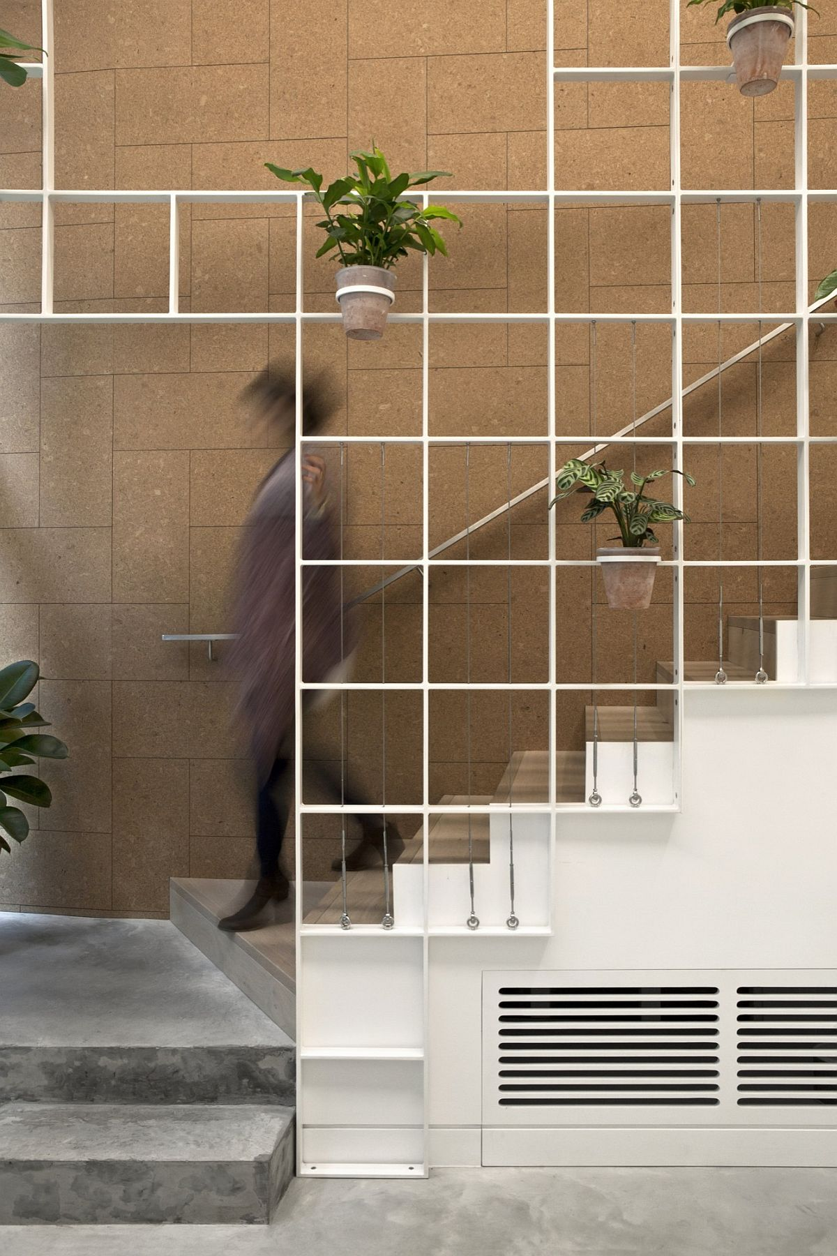 White metal grid holds plants, flowers and herbs