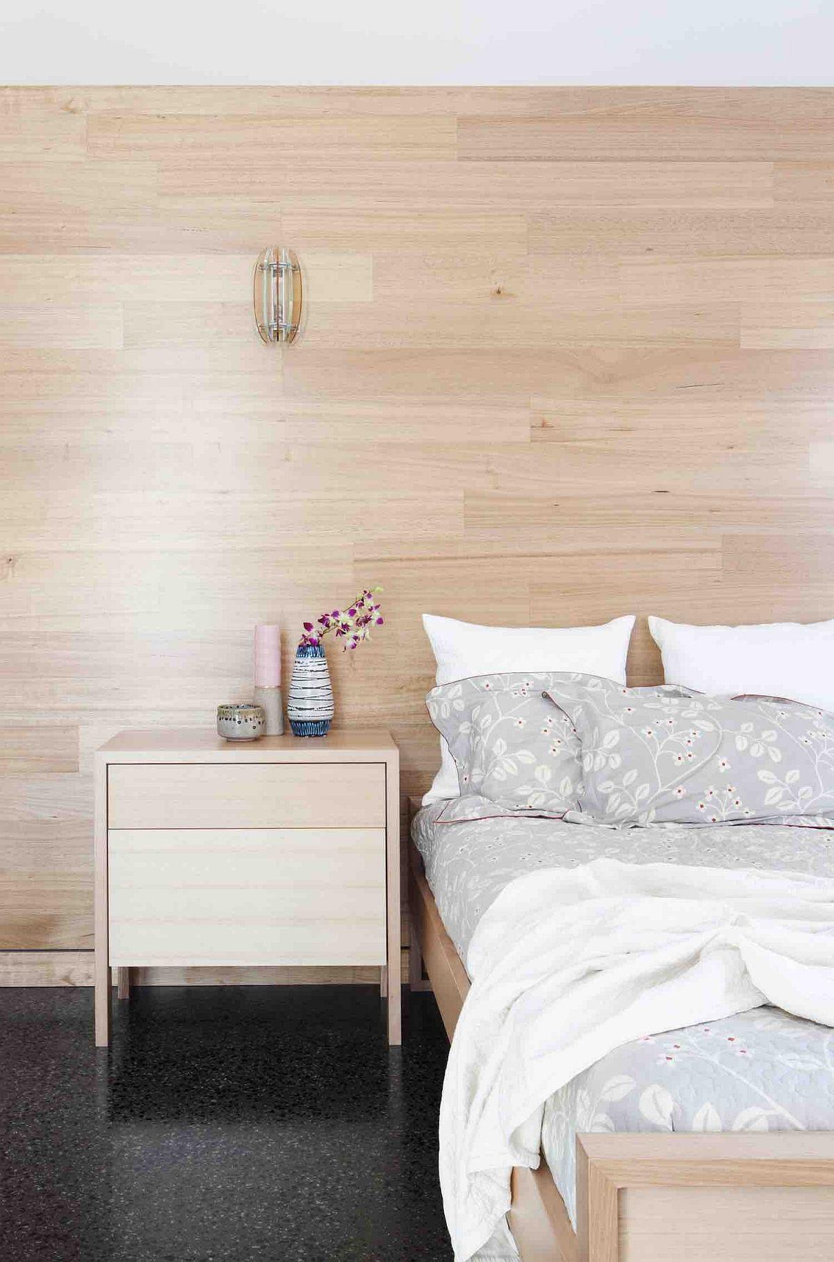 Wooden walls give the bedroom a cozy Scandinavian look