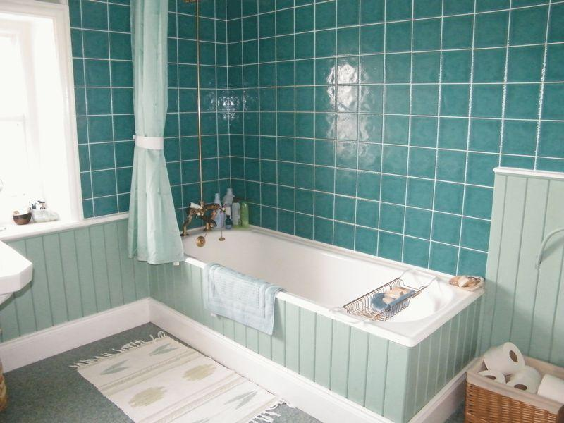 A bathroom that is a blend of different turquoise hues