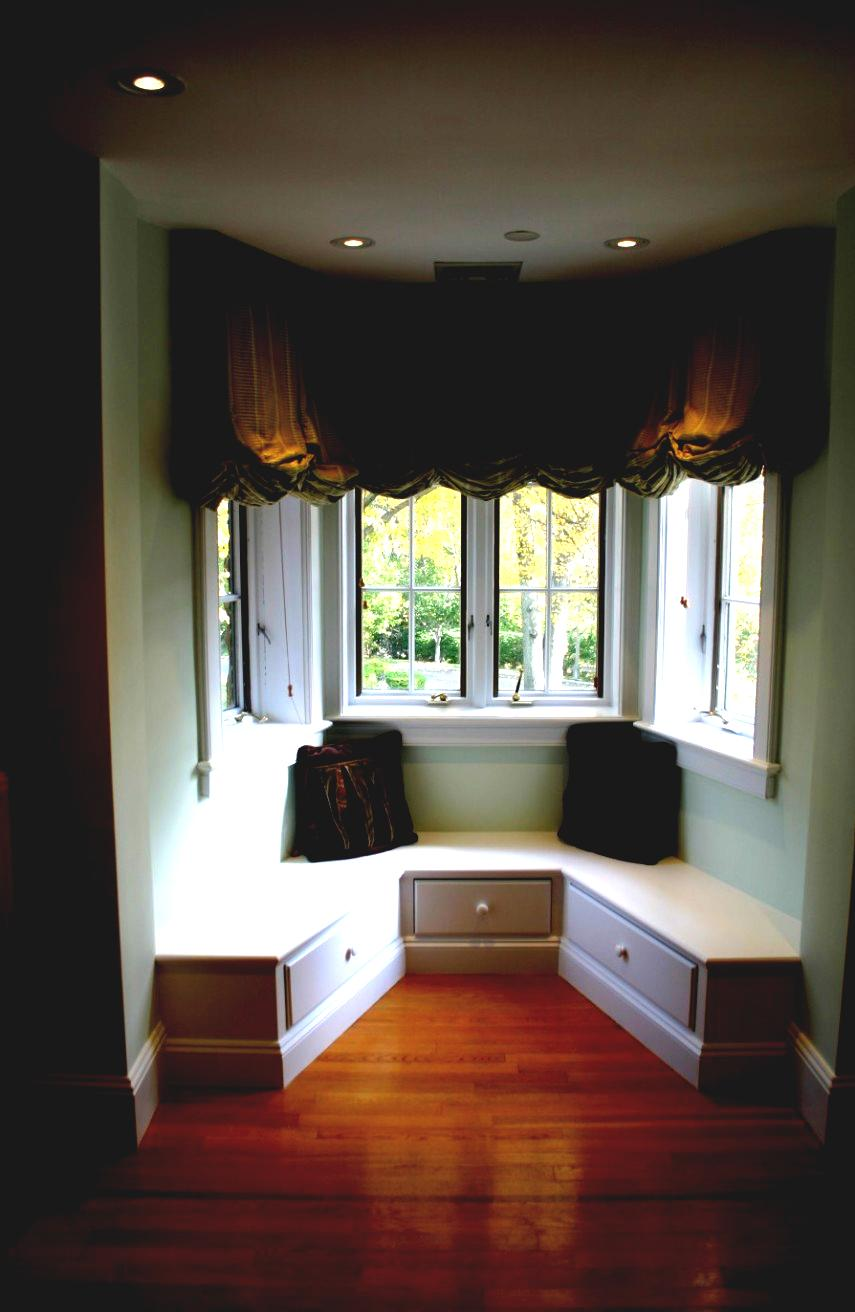 A darker room is balanced by a plain white window seat