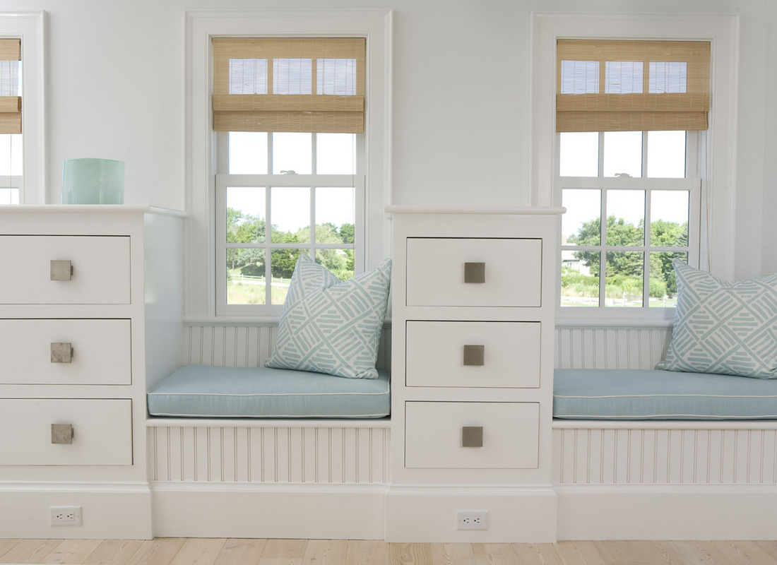A double window seat in soft pastel hues