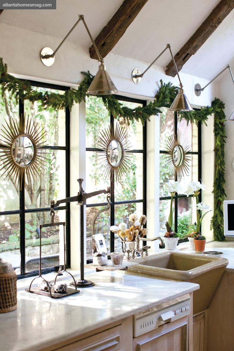 A-row-of-three-sunburst-mirrors-in-a-sunny-kitchen-