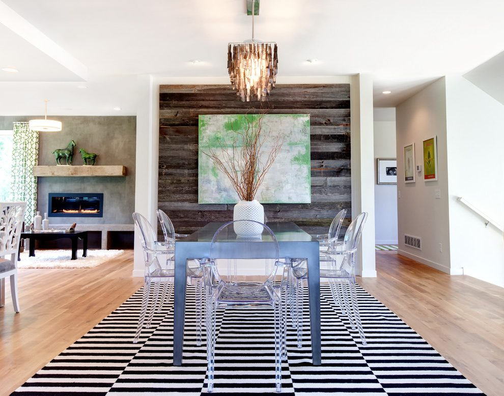 A simplistic dining room with a big striped black and white rug