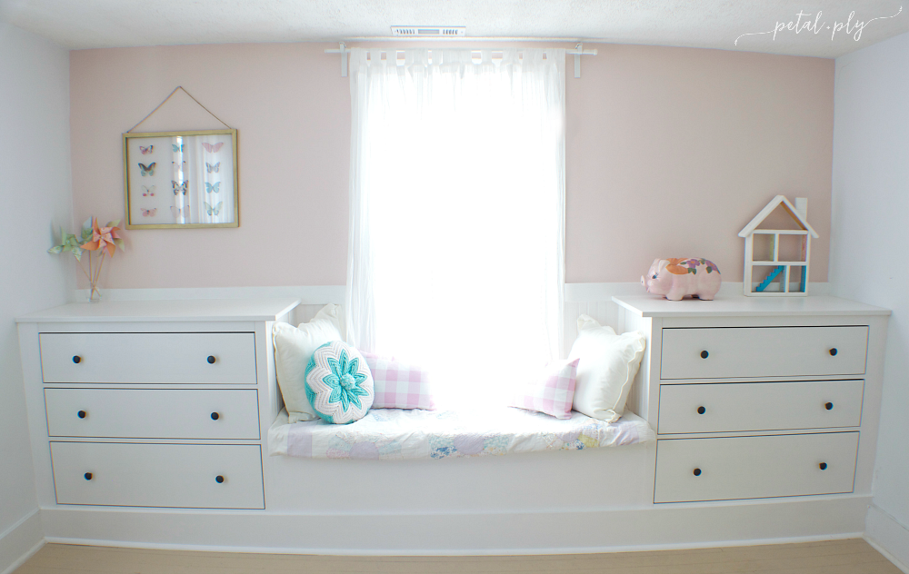 A small window seat in soft pastel colors