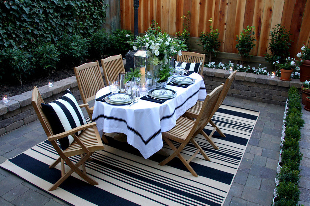 A striped rug creates an elegant outdoor dining area
