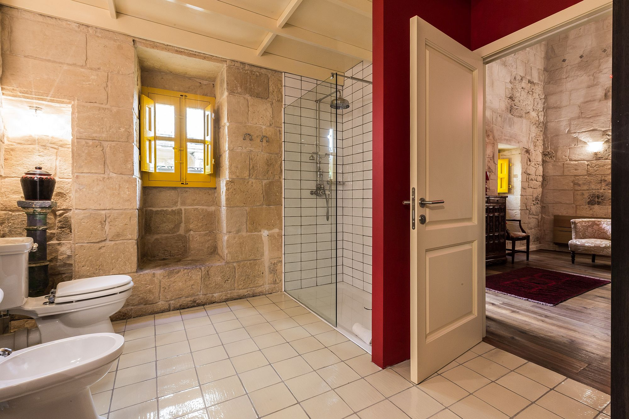 Bathroom at the first suite of Locanda La Gelsomina with stone walls, white tiles and pops of yellow and red