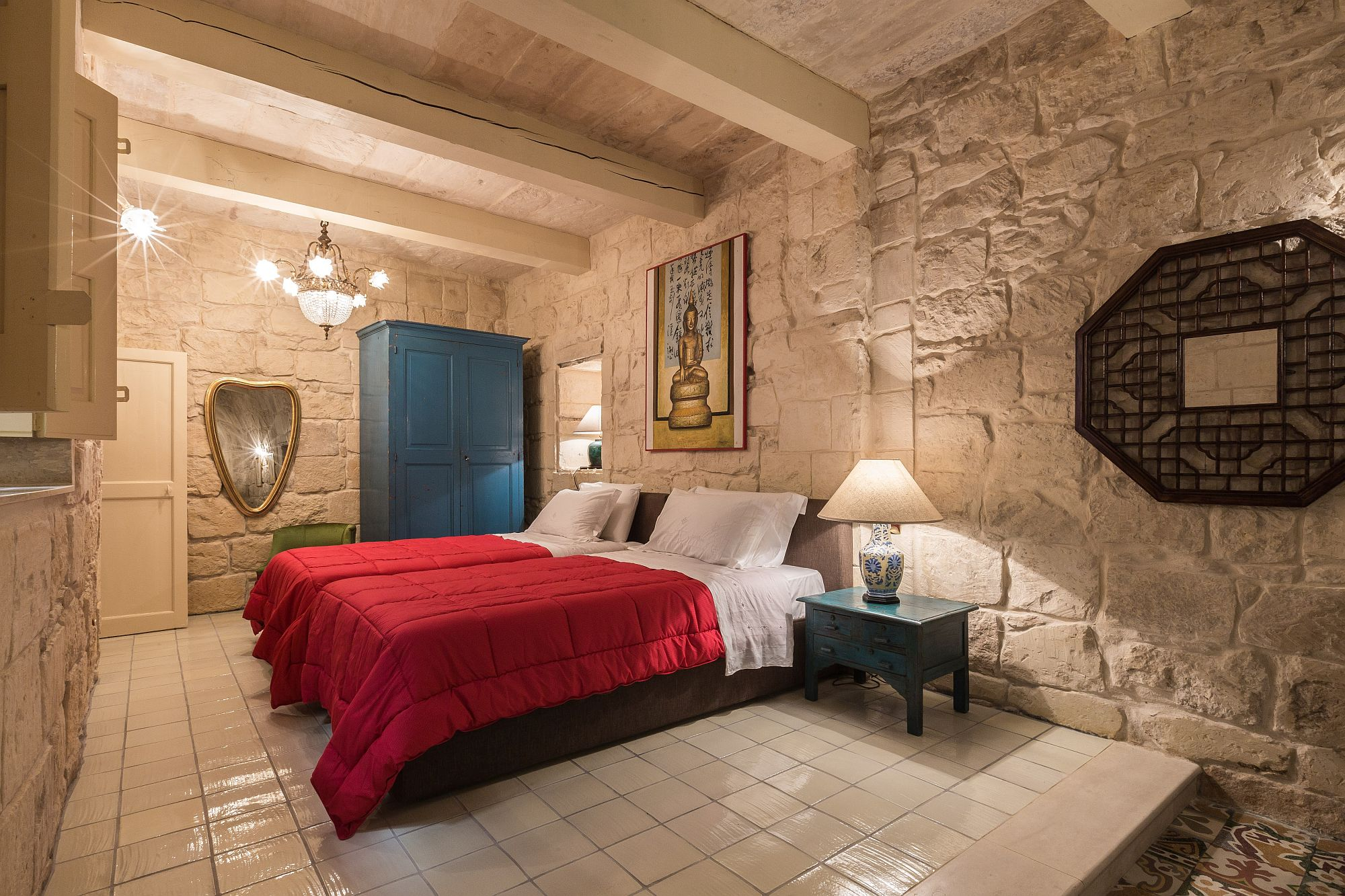 Bedroom of the second suite with traditional antique Maltese tiles, stone walls and pops of red and blue