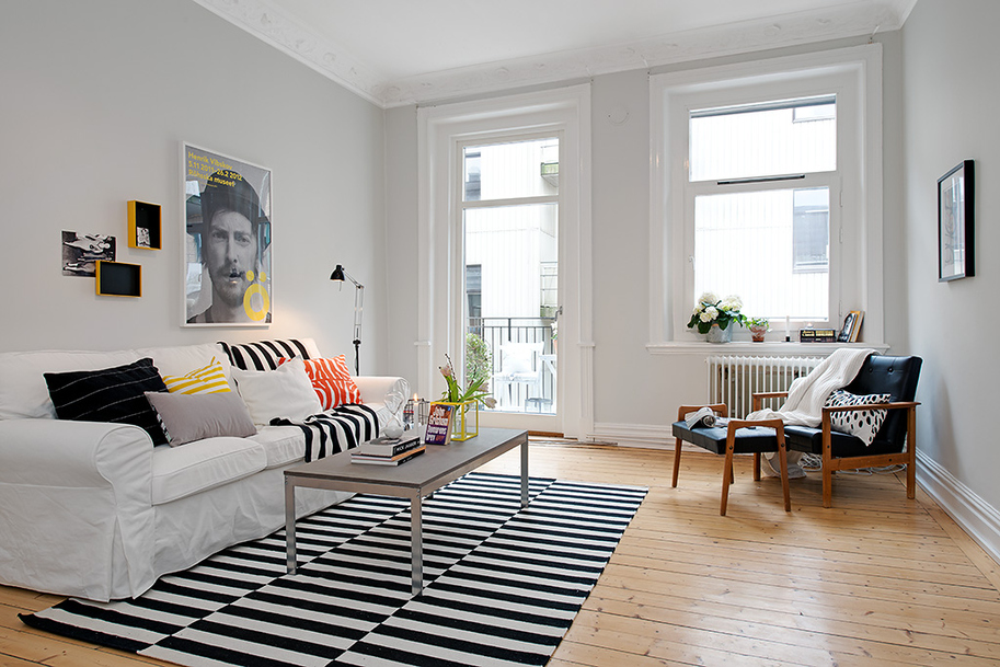 Black and white striped rug highlights the minimalism in this living room