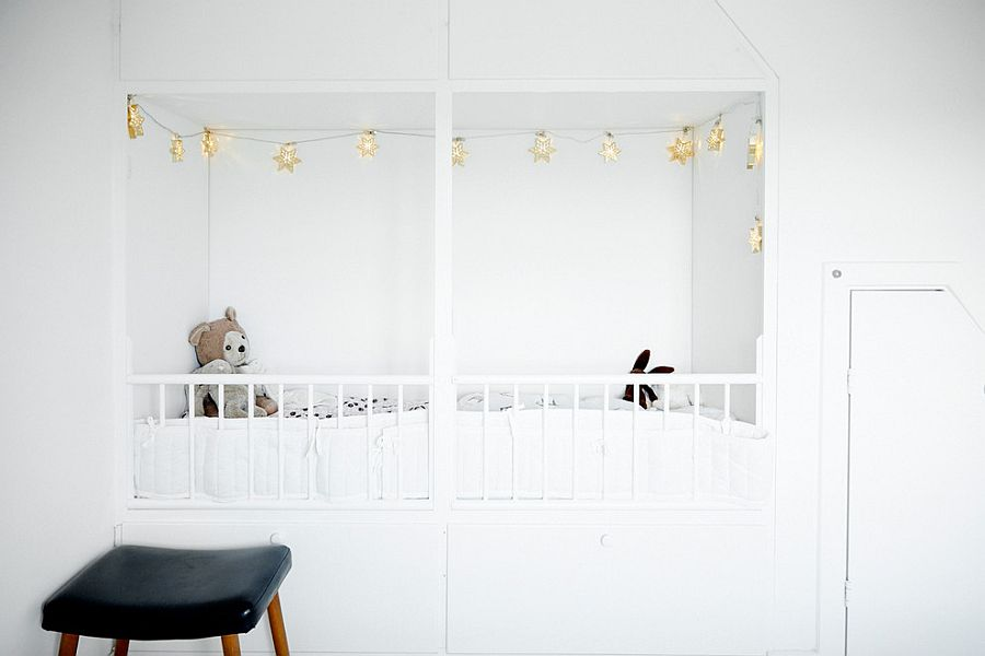 Black chair contrasts the nursery's dazzling white interior