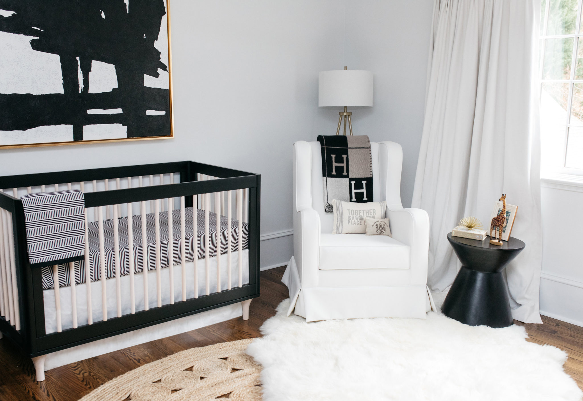 Black crib surrounded by bright decor pieces