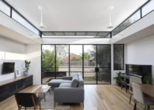 Folding-glass-doors-with-black-frame-connect-the-interior-with-the-rear-yard-217x155