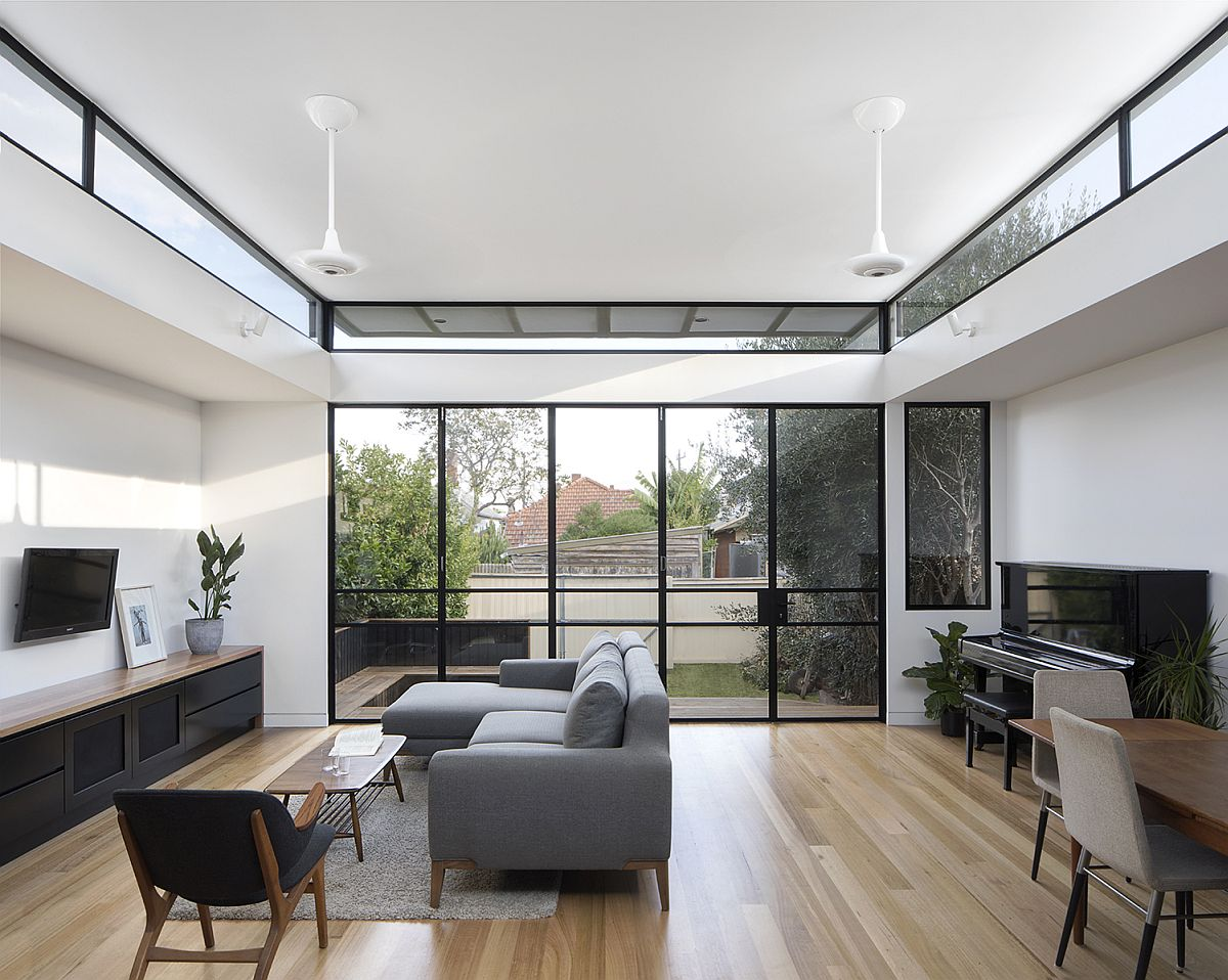 Folding glass doors with black frame connect the interior with the rear yard