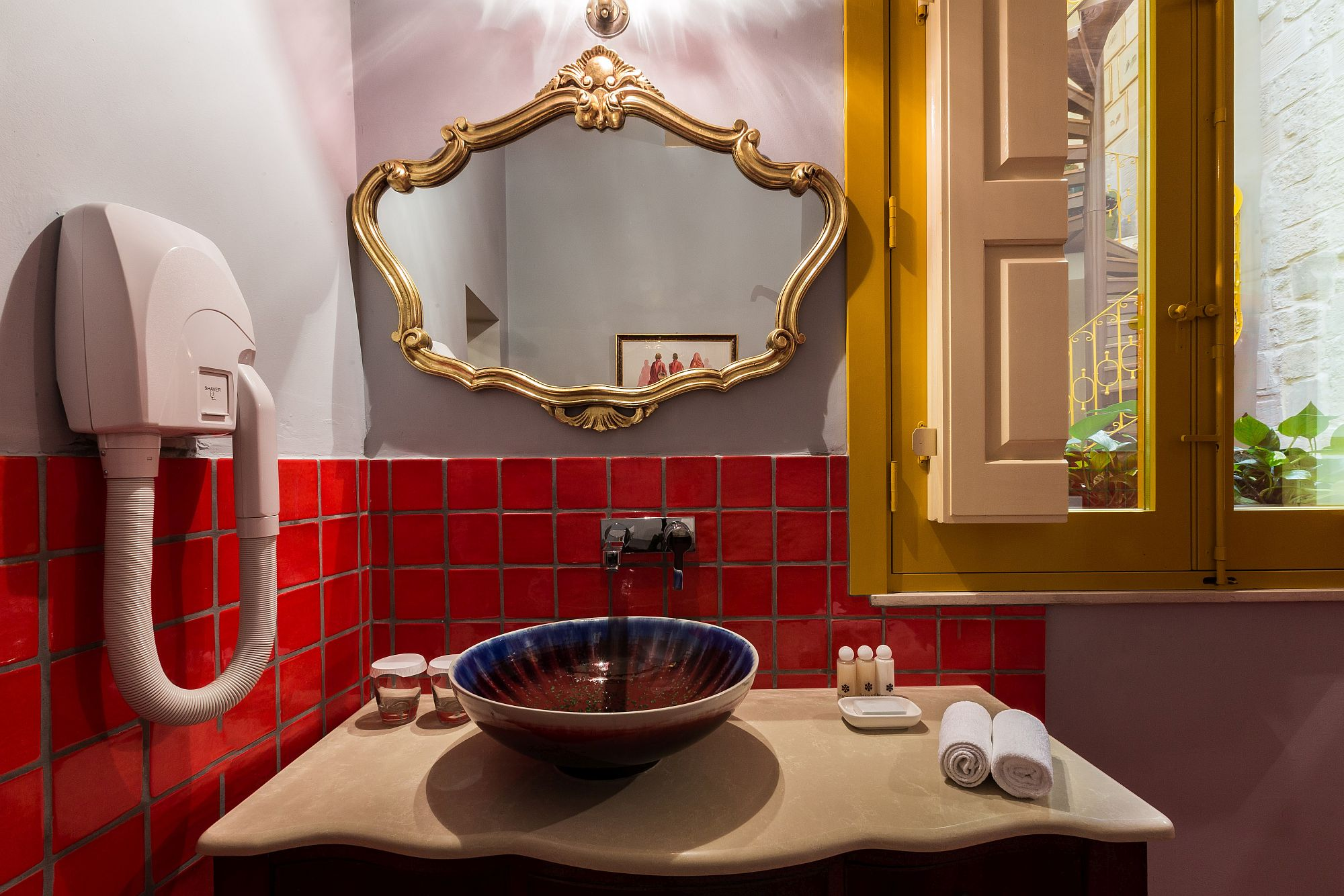 Gray and red bathroom with classic mirror and beautiful stone walls