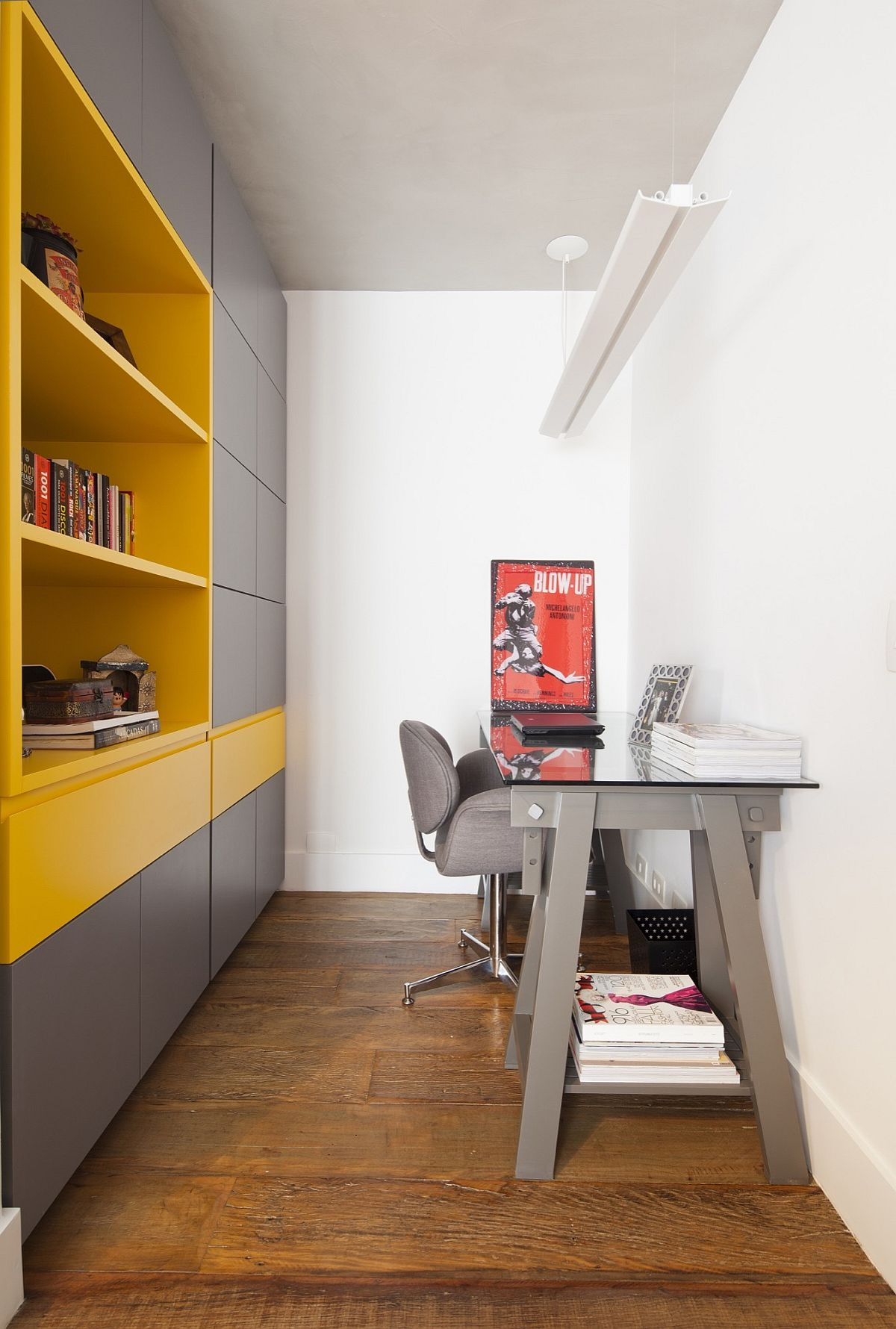 Home office with gray cabinets along with bright, open shelves in yellow