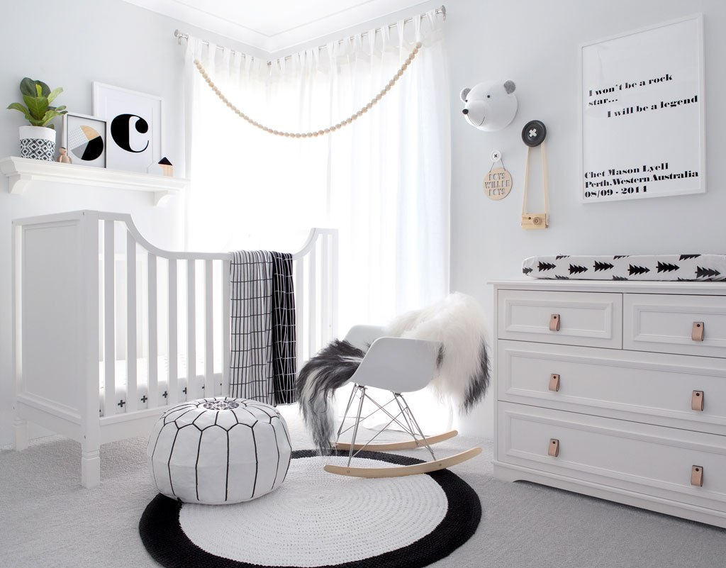 Moncohrome nursery with a round black and white rug in the center