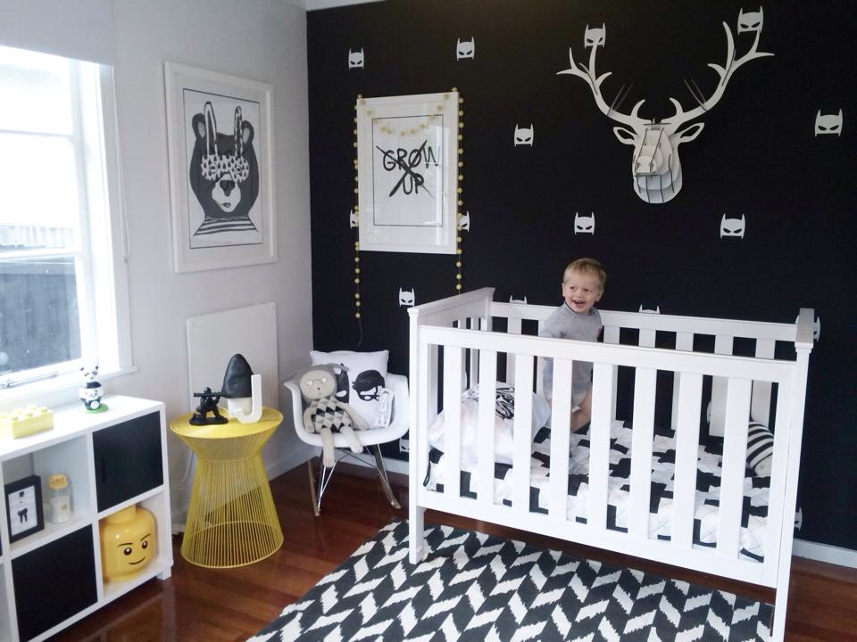 Monochrome nursery with a black wall and contrastin white pieces