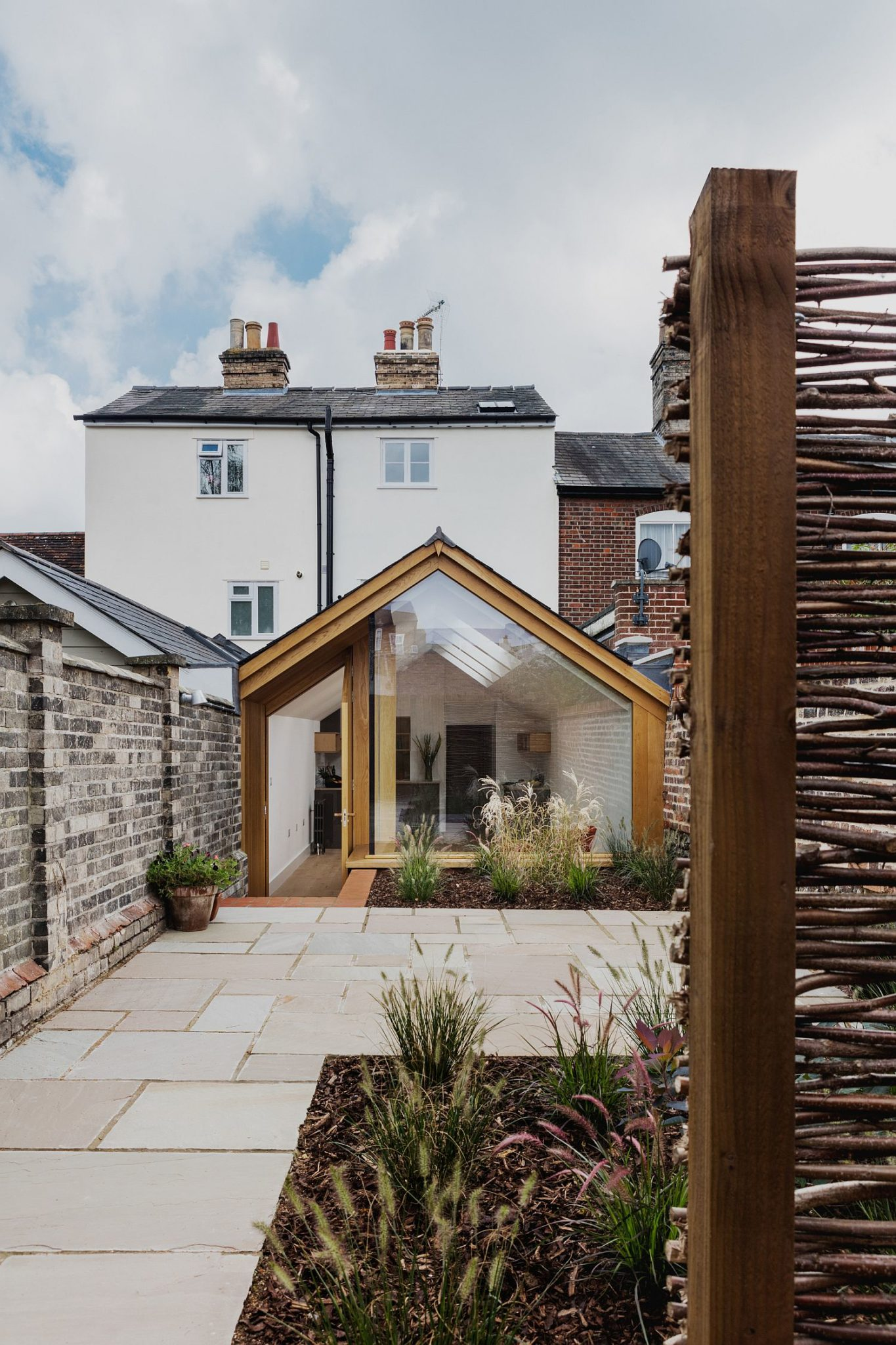 Oak-brick-and-frameless-glazing-create-an-elegant-rear-extension-to-heritage-home