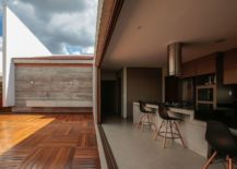 Sliding glass doors connect the long kitchen with the wooden deck outside 217x155 Cuiabá House: Open Family Home in Brazil with Shaded Outdoor Spaces