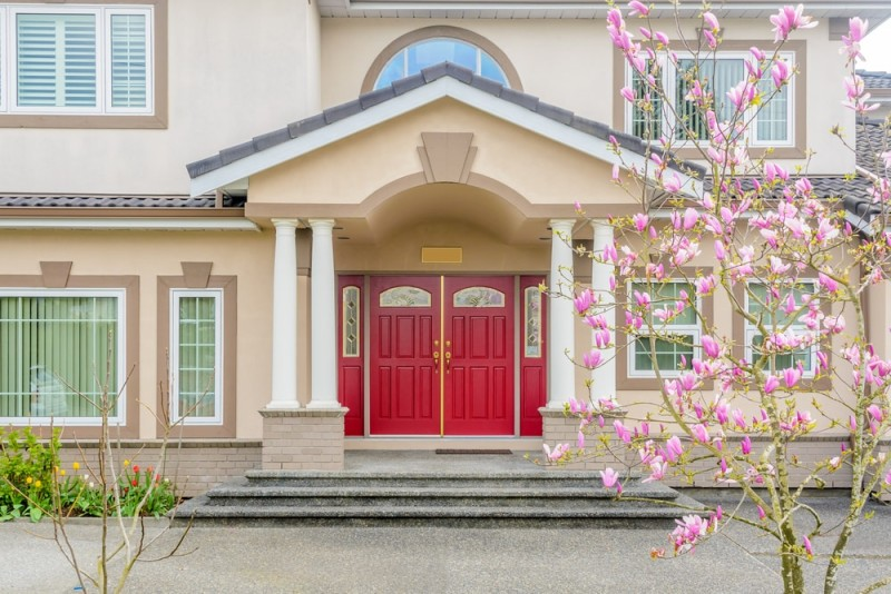 Stunning red double front doors on a beige building