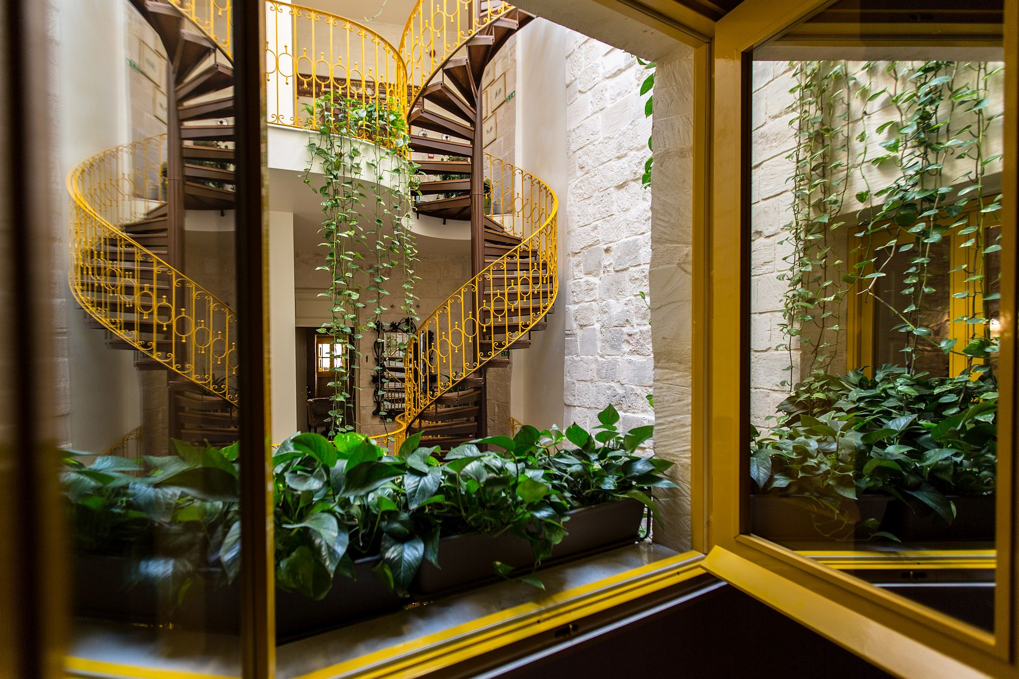 Stunning view of the spiral staircase and indoor greenery from the second suite