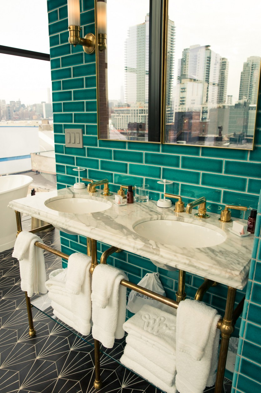 Turquoise bathroom with marble sink and golden pipes