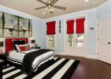 Vivid-bedroom-with-a-monochrome-rug-and-bright-red-elements--217x155