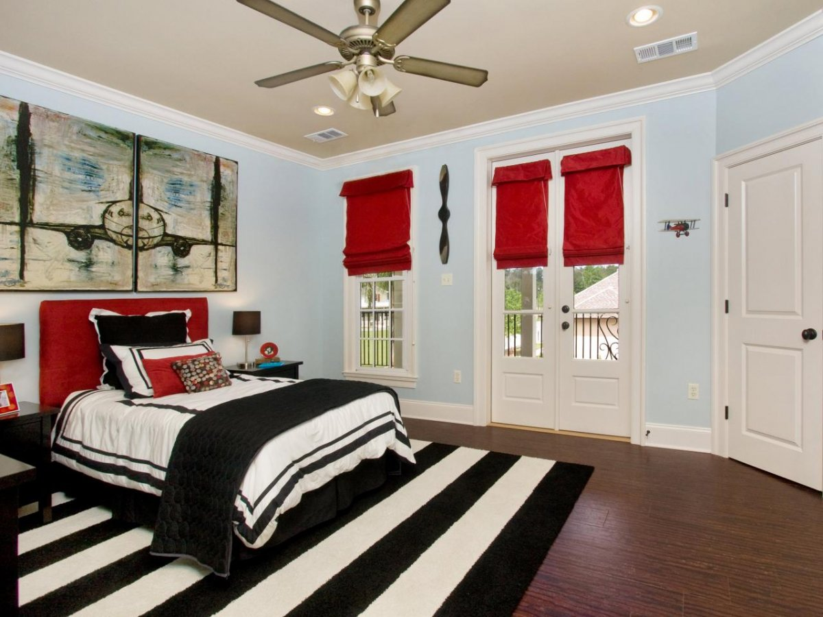 Vivid bedroom with a monochrome rug and bright red elements