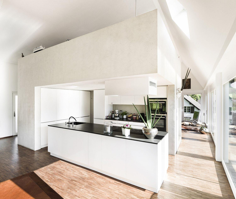 White concrete walls shape a modern, stylish kitchen