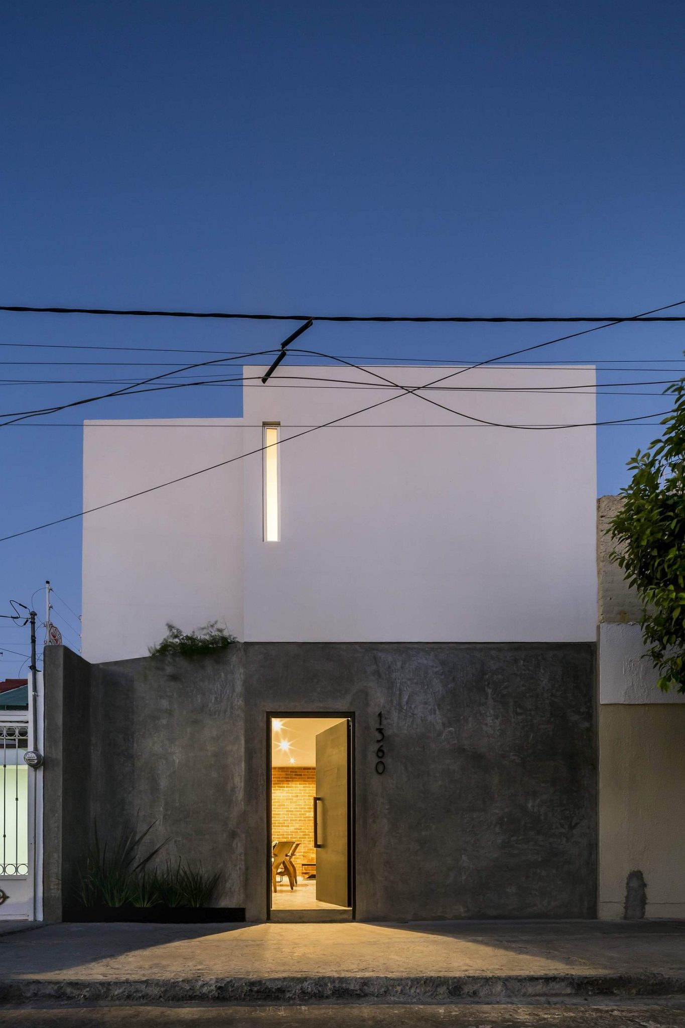 Exposed brick walls steal the show in this modern for Stucco facade
