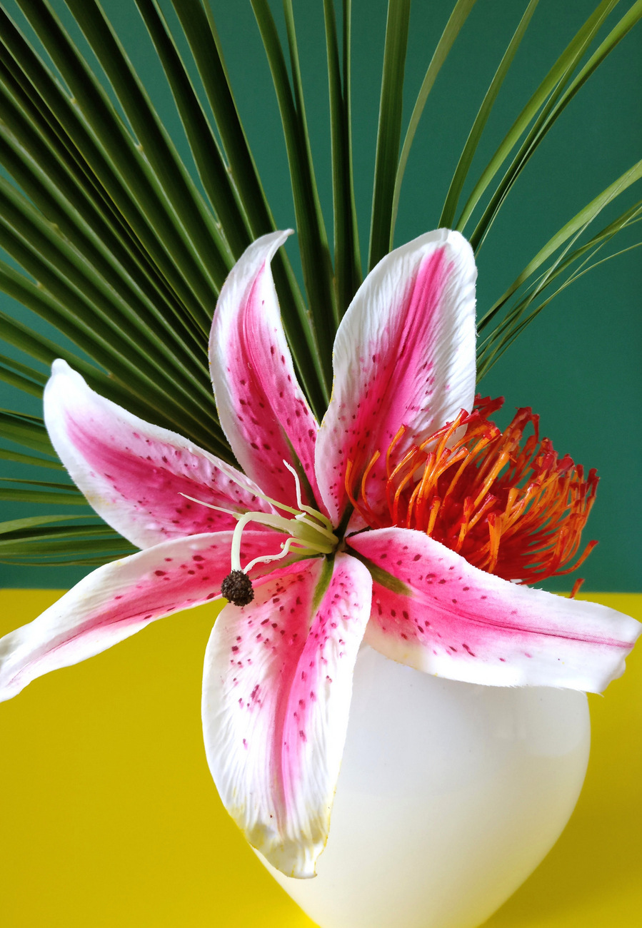 Create a tropical bouquet with greenery and flowers